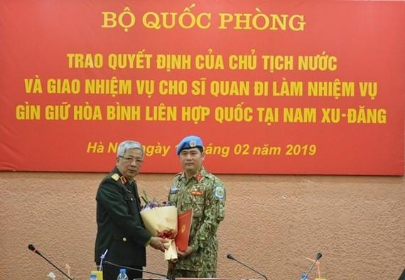 Deputy Minister of National Defence Sen. Lieut. Gen. Nguyen Chi Vinh (left) hands over the President's decision to Lieut. Colonel Nguyen Kim Tinh. (Source: qdnd.vn)