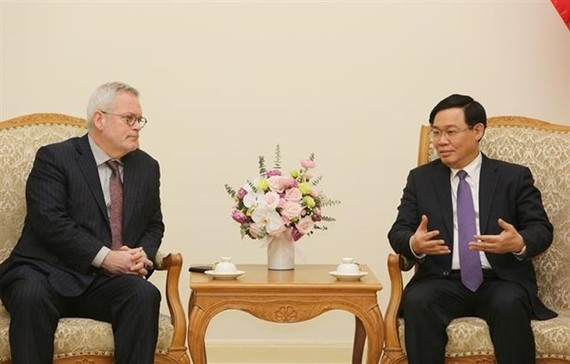 Deputy Prime Minister Vuong Dinh Hue (R) receives Charles Freeman, Senior Vice President for Asia at the US Chamber of Commerce, in Hanoi on March 8 (Photo: VNA)