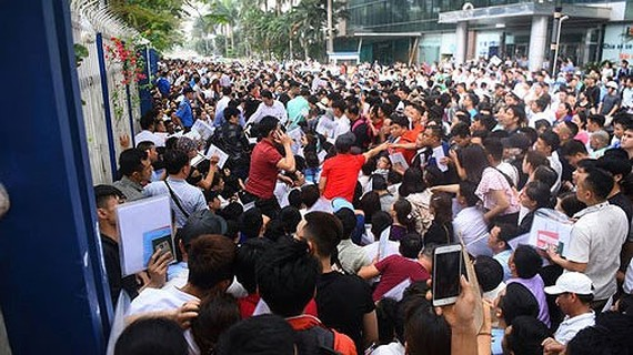 Thousands of people line up at the South korean Embassy in Hanoi to apply for visas