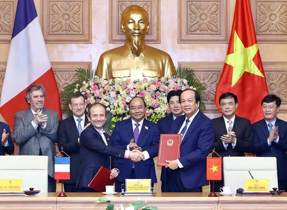 Prime Minister Nguyen Xuan Phuc (C) witnesses the signing ceremony between the Government Office of Vietnam and the French Development Agency (AFD) in e-government development cooperation (Photo: VNA)