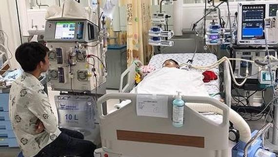 Cha của 2 bé đang thấp thỏm bên giường bệnh