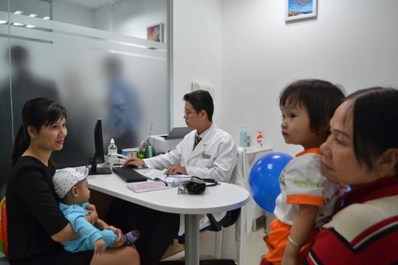Phụ huynh đưa con đi chích ngừa tại Trung tâm tiêm chủng VNVC