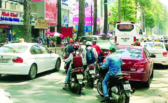Cổng Bệnh viện Từ Dũ bị lấn chiếm nên các ô tô phải đón khách dưới lòng đường,  gây khó khăn cho người tham gia giao thông