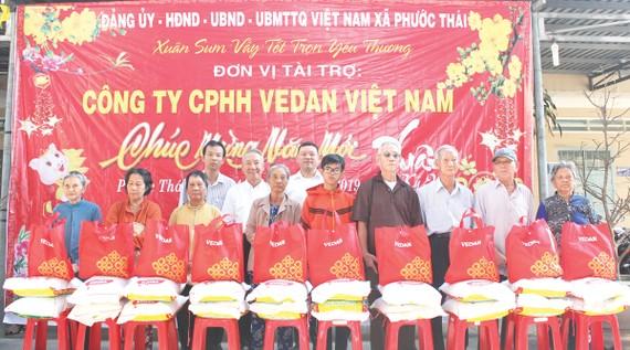 Ông Hsieh Jau Hwang - Trưởng sách lược Vedan Việt Nam (người đứng thứ 2 từ trái qua) trao quà tết cho bà con xã Phước Thái, huyện Long Thành