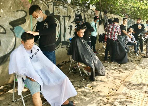 Tiệm cắt tóc miễn phí trên vỉa hè đường Phạm Văn Đồng