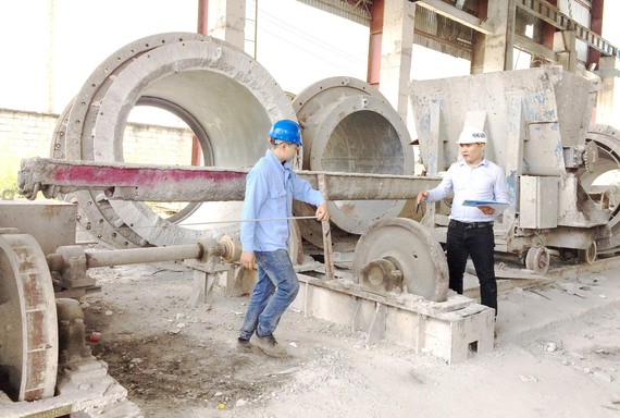 Kỹ sư Trần Quốc Toản (phải) hướng dẫn công nhân ứng dụng những cải tiến mới vào vận hành sản xuất