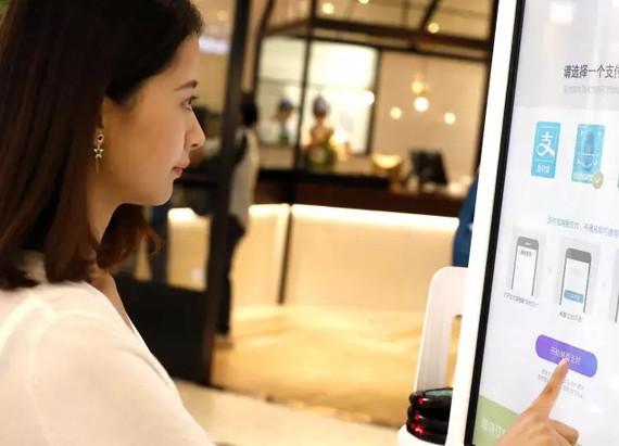 客戶刷刷臉在自助點餐機上選餐。