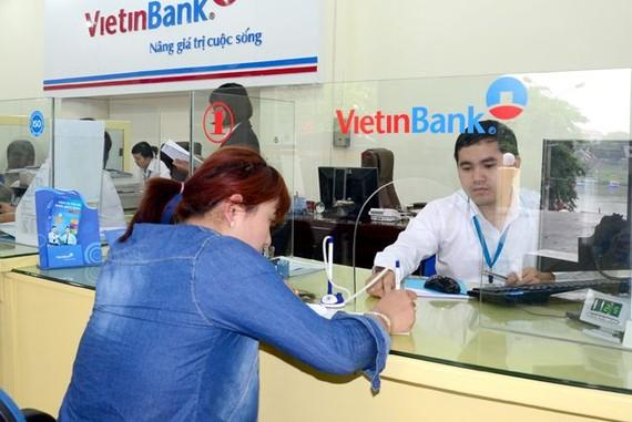 銀行人員指引客戶辦理自動支付電費服務登記手續。
