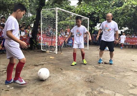 朴恒旭教練(右)指導仁平1號小學校學生踢足球。