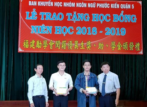 市民族處副主任梁鴻德(左一)與溫陵會館理事長 張子諒(右一)頒發獎學金給碩士生。