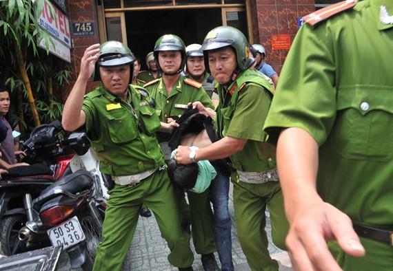 警方將抓獲的劫匪押出現場送往派出所。