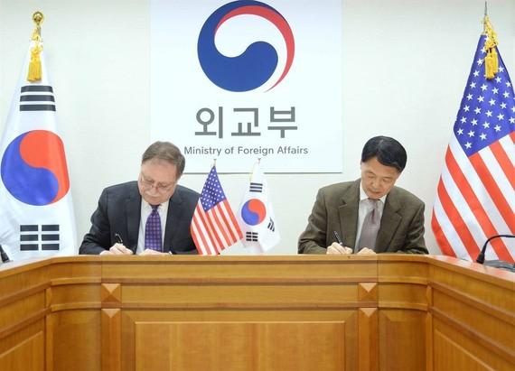 在首爾外交部大樓,張元三(右)和貝茨在協定上簽字。(圖源:韓聯社)