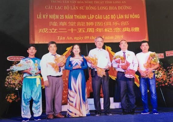 隆安省文體與旅遊廳副廳長阮氏水向隆華堂龍獅俱樂部頒贈獎狀以作鼓勵。