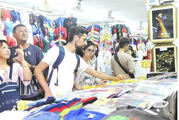 遊客在濱城市場購物。