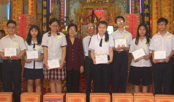 市各少數民族文學藝術協會主席劉金華及該 會館常務副理事長陳健智向瓊裔子弟頒獎。