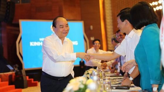 政府总理阮春福(左)同与会代表亲切握手,互致问候。(图源:PV)