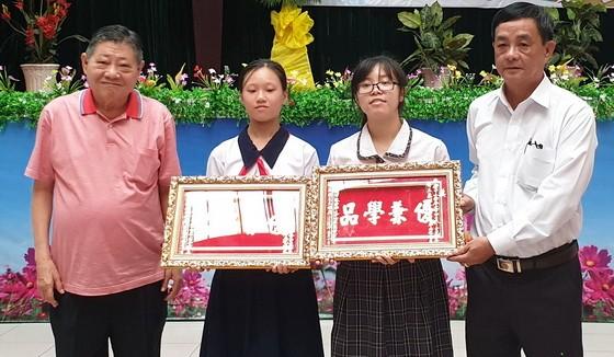 """杭慰瑤董事長(左一)向學生頒發""""品學兼優""""金牌。"""