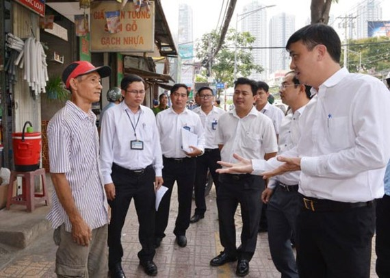 Chairman of District 7 People's Committee Le Hoa Binh (R) mobilizes residents not to encroach roads and pavements to do business in March (Photo: SGGP)