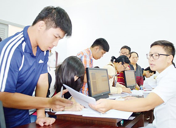 Students complete aperwork to applyfor the exam (Photo: SGGP)