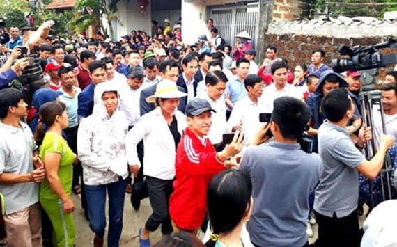 Dong Tam residents happily receiving chairman of the Hanoi People's Committee Nguyen Duc Chung who came to talk with them on April 24 (Photo: SGGP)