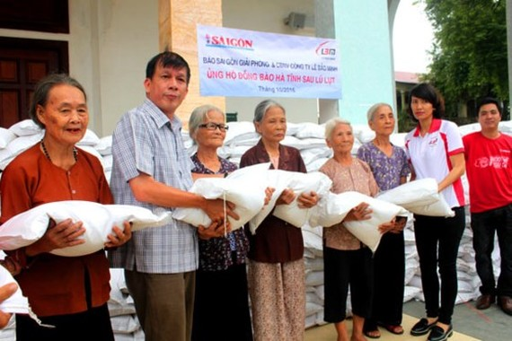 A representative of Sai Gon Giai Phong Newspaper (2nd, L) gives elderly people rice bags in Huong Khe district, the north central province of Ha Tinh where was ravaged in a flooding in October last year (Photo: SGGP)