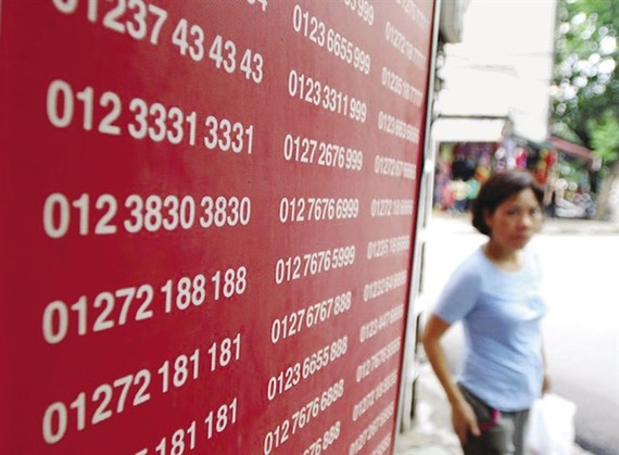 A woman walks past a board showing telephone numbers on sale. (Photo: laodong.vn)