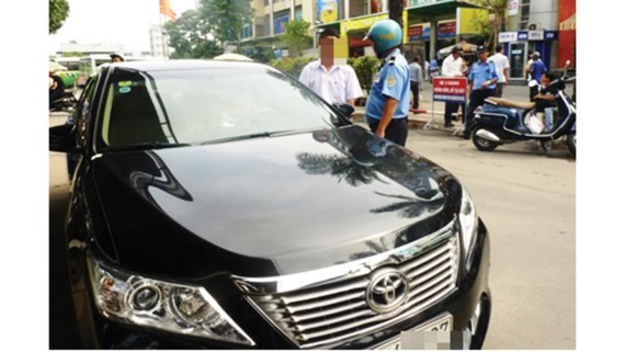 An Uber driver is fined for breaking transport business regulations (Photo: SGGP)