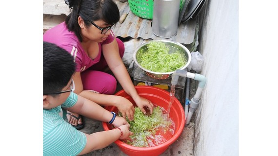 Residents use tap water in Phuoc Kien commune, Nha Be district, HCMC (Photo: SGGP)