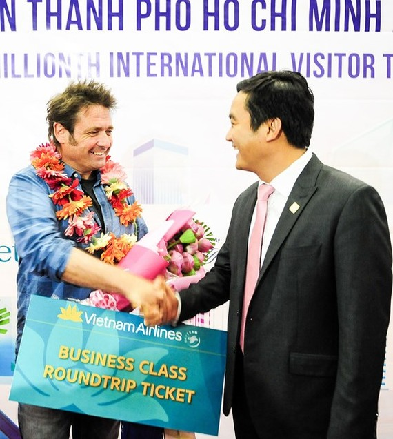 Mr. Bui Ta Hoang Vu, director of the Department of Tourism, congratulates the six millionth visitor to HCMC this year on December 15 (Photo: SGGP)