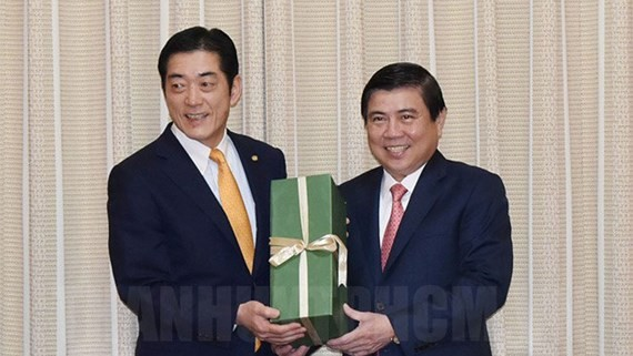 HCMC People's Committee chairman Nguyen Thanh Phong (R) gives governor of Japanese Ehime province Tokihiro Nakamaraa souvenir (Photo: thanhuytphcm.vn)