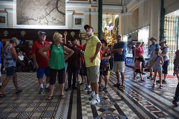 A tour guide with a group of tourists at the Central Post Office in HCM City. Photo: VNS