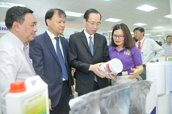 Standing deputy chairman of HCMC People's Committee Le Thanh Liem sees products sold at the goods supply, demand connectivity conference 2018 in Ben Tre province on November 22 (Photo: SGGP)
