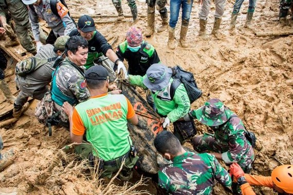 Rescue workers carry a body bag containing remains of victims following a landslide at Cisolok district in Sukabumi (Source: Reuters/ANTARA)