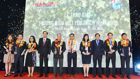Standing Deputy Chairman of the Ho Chi Minh City People's Committee Le Thanh Liem and SGGP's editor in chief Nguyen Tan Phong give the Most Favorite Vietnamese Brands Awards to enterprises. (Photo: SGGP)