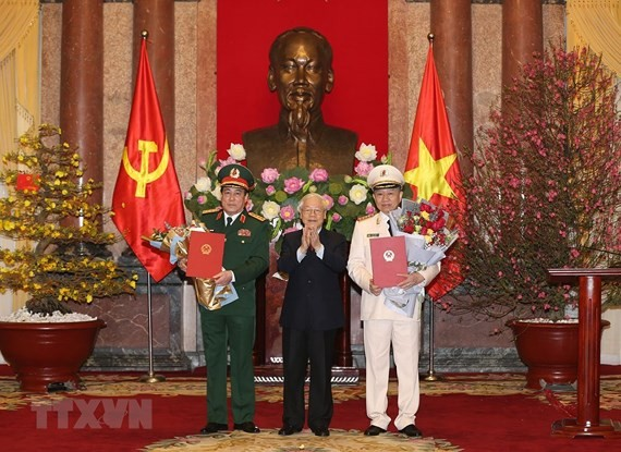 Party General Secretary and President Nguyen Phu Trong, who is also Secretary of the Central Military Commission and Chairman of the National Defence and Security Council, hands over the promotion decisions to the officers during a ceremony in Hanoi yeste
