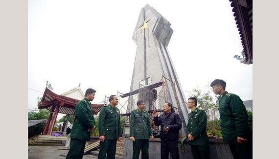 Mr. Hoang Nhu Ly (3rd, R) and soldiers at Po Hen Border Post talk together by Po Hen Monument (Photo: SGGP)