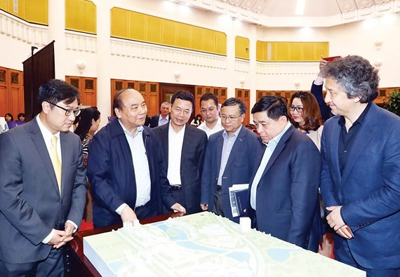 PM Nguyen Xuan Phuc (second from left) and participants examine the model of the National Innovation Centre.(Photo: VNA)