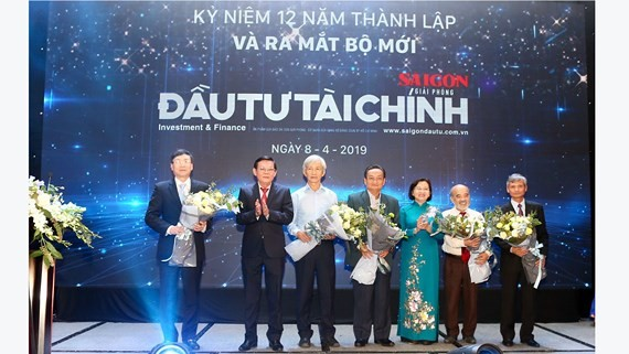 Ms. Than Thi Thu, head of HCMC Party Committee's Propaganda and Education Board and Mr. Nguyen Tan Phong, editor in chief of Sai Gon Giai Phong Newspaper give flowers to experts at the ceremony (Photo: SGGP)