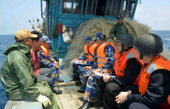 Vietnamese, Chinese coast guards inspect a Vietnamese fishing vessel in the Gulf of Tonkin (Photo: VNA)