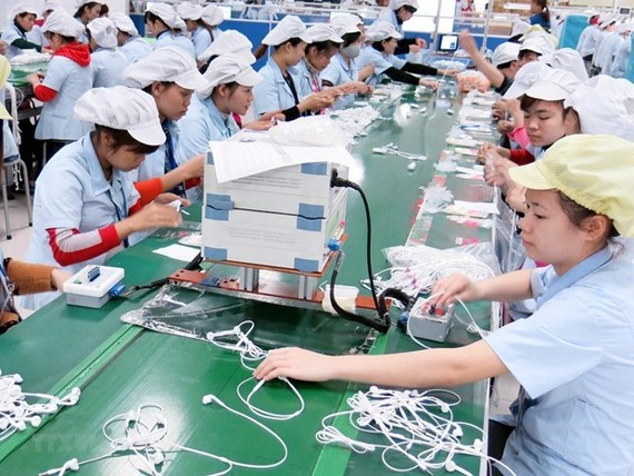 Workers produce headphones at a Samsung factory (Photo: VNA)