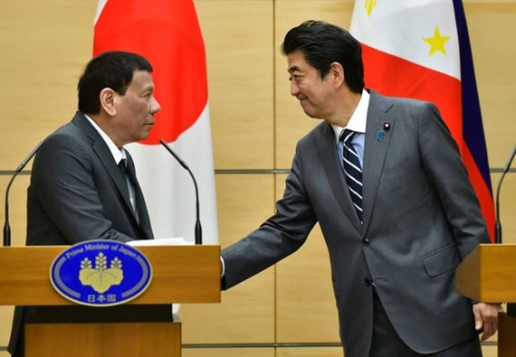 Philippine President Rodrigo Duterte (L) greets Prime Minister Shinzo Abe during a joint press statement in Tokyo on May 31 (Source: Reuters)