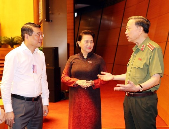 NA Chairwoman Nguyen Thi Kim Ngan (centre) and Minister of Public Security To Lam (R) discuss before the session begins (Photo: VNA)