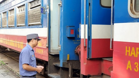 A station staff waiting outside the train to Dong Dang at Gia Lam station. Photo: SGGP