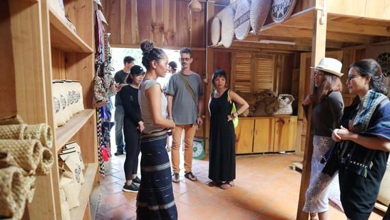 Du khách tham quan gian trưng bày sản phẩm dệt thổ cẩm, cà phê arabica của người K'Ho dưới chân núi Langbiang