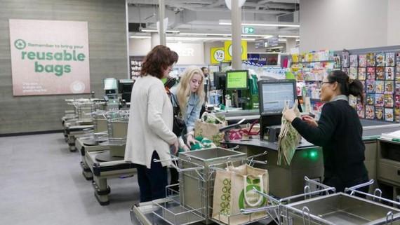 Khách hàng thanh toán tại một siêu thị Woolworths không dùng túi nhựa miễn phí ở Sydney, Úc. Ảnh: REUTERS