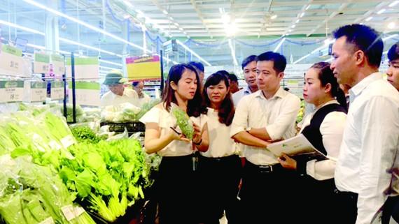 Nhân viên BigC tập huấn tại quầy mặt hàng rau ăn lá cho các hộ sản xuất huyện Nhà Bè.  Ảnh: Hải Hà