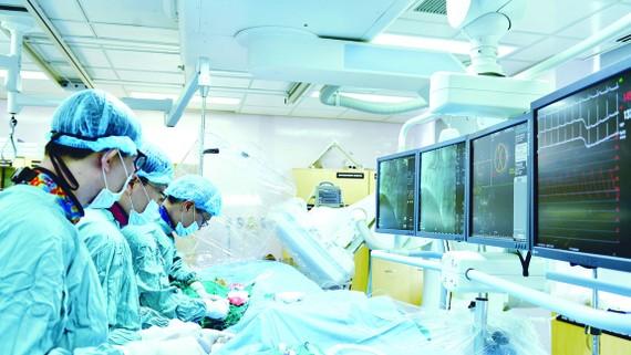 Bác sĩ Bệnh viện Đại học Y Dược TPHCM hướng dẫn bác sĩ  Bệnh viện Đa khoa Sóc Trăng phương pháp can thiệp tim mạch.   Ảnh: THÀNH AN