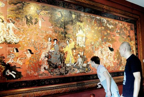 Khách tham quan xem tác phẩm sơn mài Vườn xuân Trung - Nam - Bắc  của danh họa Nguyễn Gia Trí. Ảnh: AN DUNG