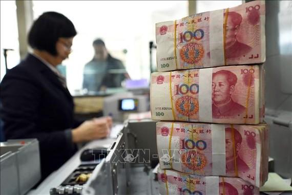 Kiểm đồng 100 Nhân dân tệ tại ngân hàng ở tỉnh Giang Tô. Ảnh: AFP/TTXVN