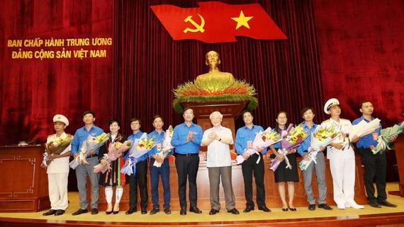 Tổng Bí thư, Chủ tịch nước Nguyễn Phú Trọng tặng hoa các đảng viên trẻ tiêu biểu. Ảnh: TTXVN